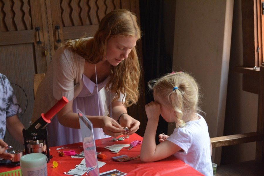 A volunteer helping a child make a button